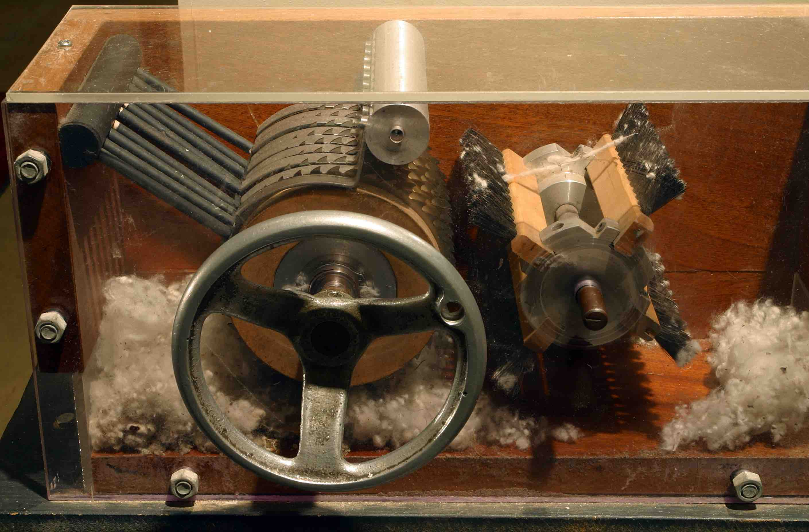 The cotton gin has multiple gears in it with fairly sharp spokes, and a hand-turned wheel. As you feed cotton in on one side, and turn the wheel, it pulls the cotton through the gears/spokes, and separates out seeds