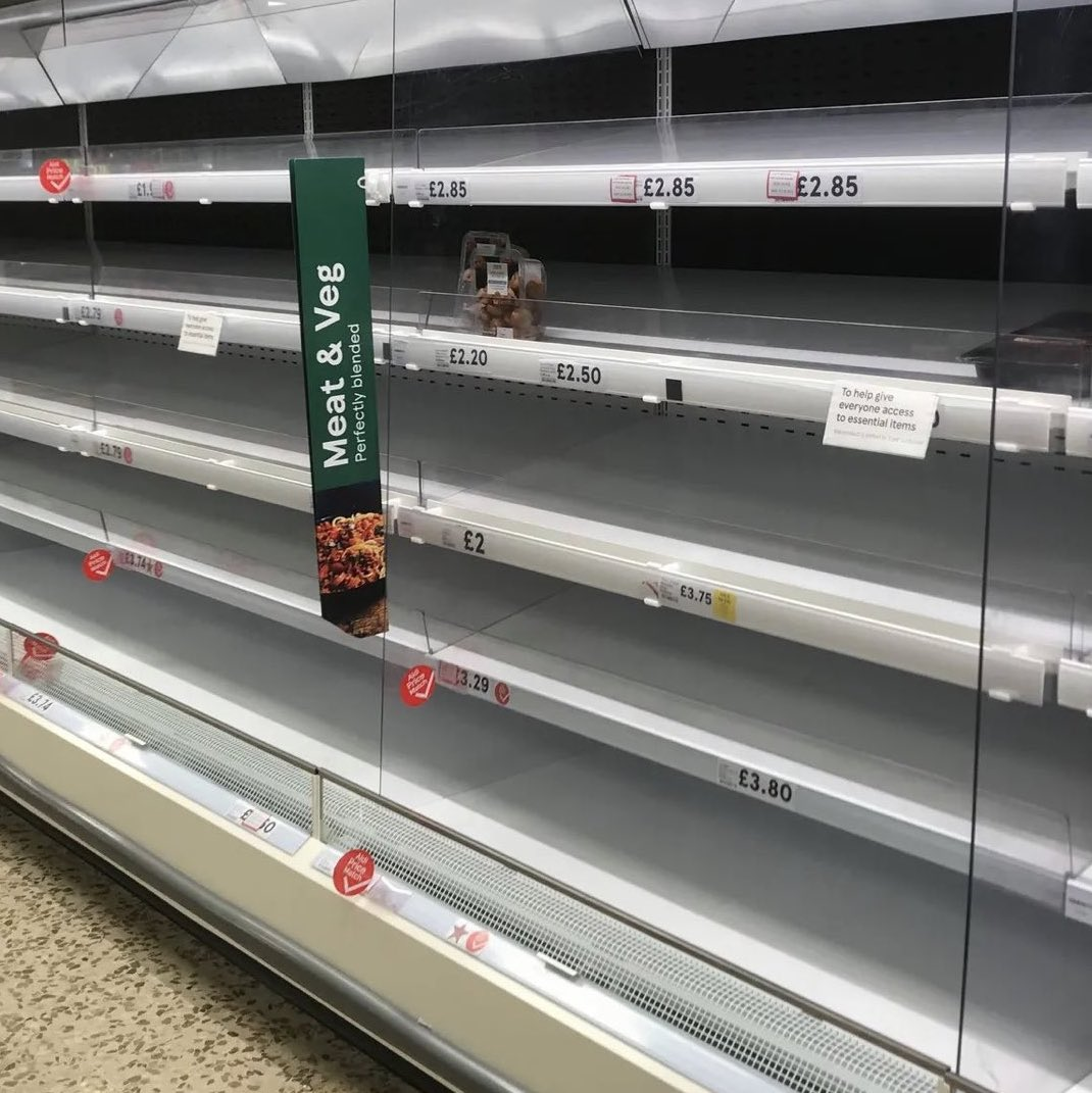 A bunch of empty shelves, with  prices listed in pounds sterling