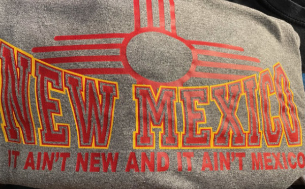The shirt says 'New Mexico: It ain't new, and it ain't Mexico'